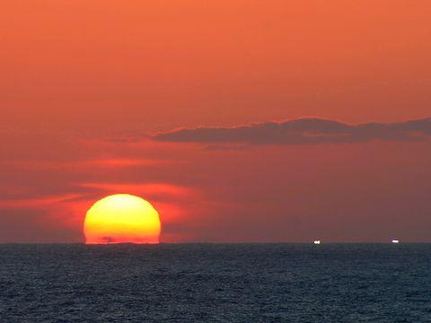 日本海に沈む夕日とイカ釣り漁船の漁り火/香美町香住区 香住海岸